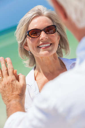 Happy senior woman with perfect teeth dancing with man in a couple and holding hands on a deserted tropical beach with bright clear blue sky photo