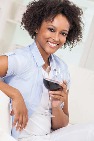 A beautiful happy mixed race African American girl or young woman drinking red wine at home on a white sofa photo
