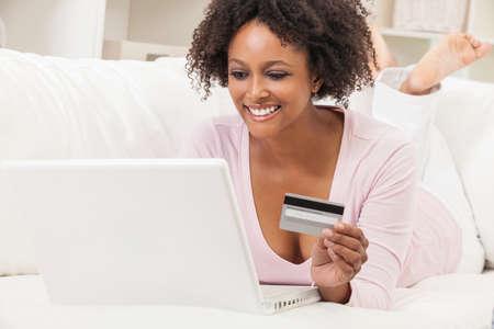 Eine schöne glückliche gemischte Abstammung African American Mädchen oder eine junge Frau, die Festlegung auf Sofa mit einem Laptop-Computer-Shopping auf Linie mit ihrer Kreditkarte Standard-Bild - 32857589