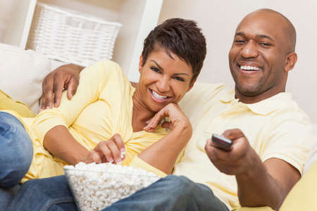 A happy African American man and woman couple in their thirties sitting at home using a remote control, eating popcorn and watching a movie or television Imagens