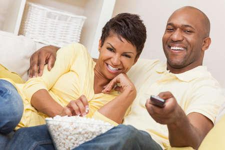 parejas de amor: Un hombre y una mujer feliz pareja afroamericana en sus treinta a�os sentado en su casa usando un mando a distancia, comiendo palomitas y viendo una pel�cula o la televisi�n Foto de archivo