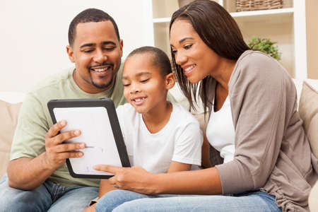 African American family, parents and son, having fun using tablet computer together Archivio Fotografico