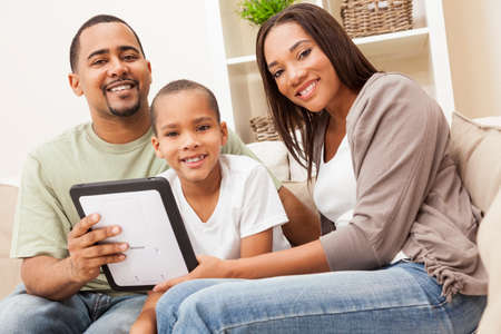 African American family, parents and son, having fun using tablet computer together Standard-Bild