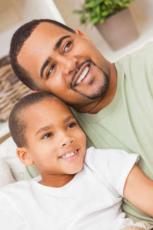 A happy African American man and boy, father and son, family sitting together at home photo