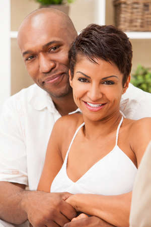 A happy African American man and woman couple in their thirties sitting at home, the woman is in focus in the foreground the man out of focus in the background. Stock Photo