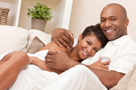 A happy African American man and woman romantic couple in their thirties cuddlng embracing at home.