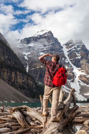 Hiking man with rucsac backpack standing on tree log by Moraine Lake looking at snow covered Rocky Mountain peaks, Banff National Park, Alberta Canada photo