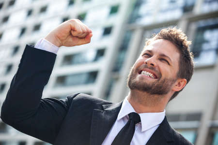 business success: A young successful man, male executive businessman arms raised celebrating cheering shouting in front of a high rise office block in a modern city Stock Photo