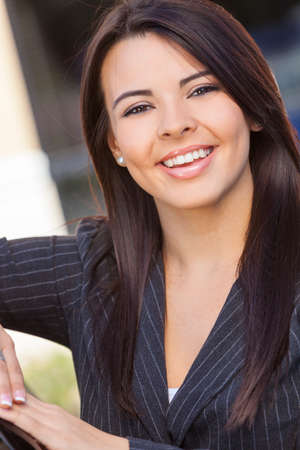 Outdoor portrait of a beautiful young Latina Hispanic business woman or businesswoman smiling photo