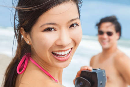 Man & woman Asian couple, boyfriend girlfriend in bikini, taking vacation video or photograph at the beach Stock Photo