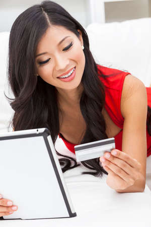 woman in red dress: Beautiful Asian Chinese woman using a credit card for on line shopping on the internet with a tablet computer Stock Photo