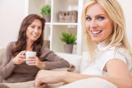 Amigos de dos hermosas mujeres en casa bebiendo té o café juntos