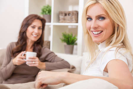 women holding cup: Two beautiful women friends at home drinking tea or coffee together Stock Photo