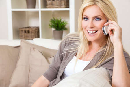 A beautiful young woman talking on her cell phone at home photo