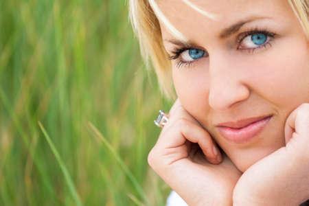blonde yeux bleus: Un beau modèle blond aux yeux bleus contre un fond d'herbe verte naturelle