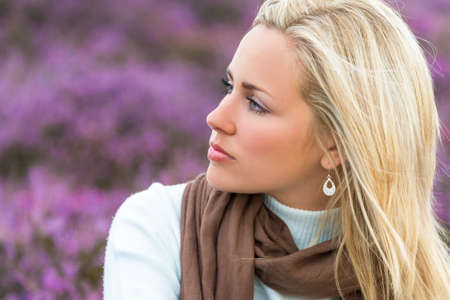 Una mujer rubia joven naturalmente hermosa en un campo de flores de color púrpura brezo