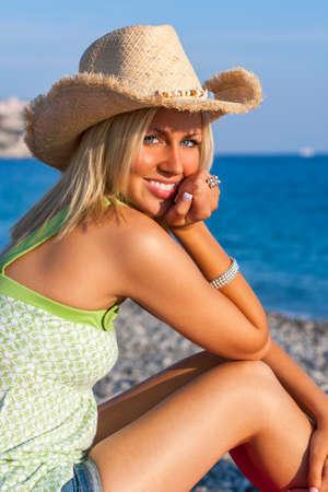 Schöne blonde junge Frau oder ein Mädchen in ihren Zwanzigern glücklich lächelnd tragen Stroh Cowboy Hut sitzt auf einem Strand mit blauem Meer