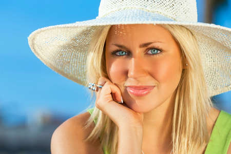 blonde  blue eyes: Beautiful blond young woman or girl in her twenties happy smiling wearing sun hat resting on her hand in sunshine on summer day with blue sky