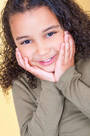 cheeky: Studio shot of a beautiful young mixed race African American girl smiling and looking cheeky with hands on her face Stock Photo