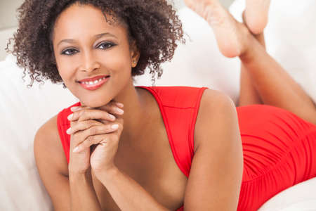 girl in red dress: A beautiful mixed race African American girl or young woman wearing a red dress looking happy and smiling