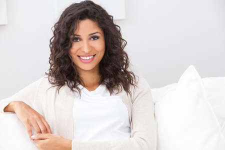 Portrait of a beautiful young Latina Hispanic woman smiling with perfect teeth sitting on a white sofa
