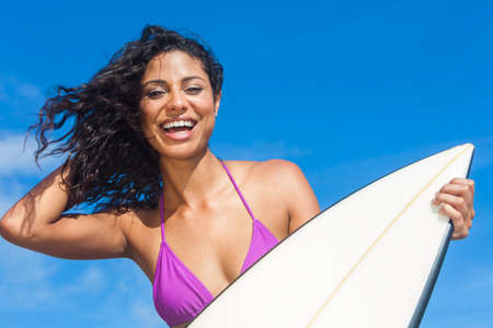 latina: Beautiful young woman surfer girl in bikini with surfboard laughing ready to surf on a beach