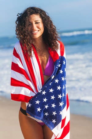 summer holiday bikini: Beautiful young woman laughing wearing bikini and wrapped in American flag towel on a sunny beach Stock Photo
