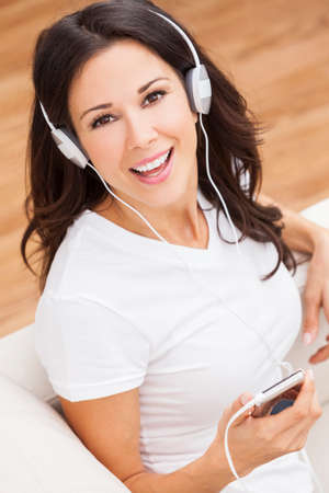 sexy headphones: A beautiful happy girl or young woman sitting down listening to music on mp3 player and headphones