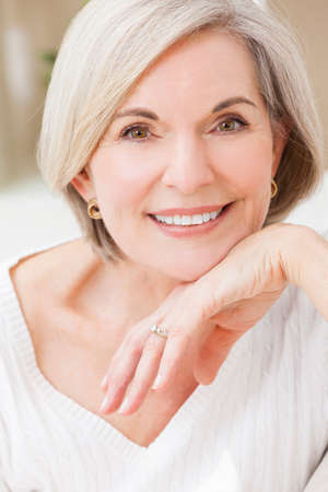 attractive female: Portrait of an attractive elegant senior woman relaxing at home. Stock Photo