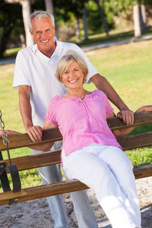 happy senior couple: Happy senior man and woman couple sitting together outside in sunshine on a park bench Stock Photo