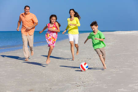 women playing soccer: A happy family of mother, father and two children, son and daughter, running playing soccer or football in the sand of a sunny beach