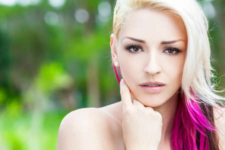 nude outdoors: Outdoor portrait of a beautiful young woman or girl with brown eyes, blond and magenta pink hair Stock Photo