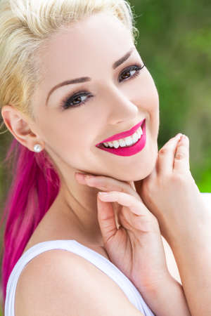 brown eyes: Outdoor portrait of a beautiful smiling woman or girl with brown eyes, perfect teeth, blond and magenta pink hair