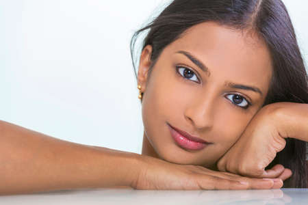 Portrait of a beautiful young Indian Asian woman or girl resting on her hand Stock Photo