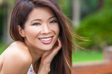 resting: Outdoor portrait of a beautiful young Chinese Asian young woman or girl with perfect teeth, smiling and resting in her hand Stock Photo