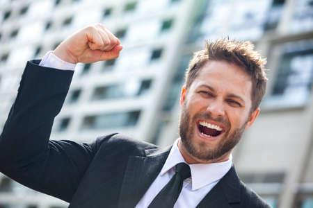 cheer: A young successful man, male executive businessman arms raised celebrating cheering shouting in front of a high rise office block in a modern city Stock Photo
