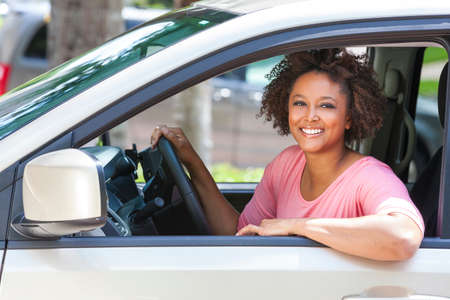 african american woman smiling: Beautiful young mixed race black African American woman driving a car