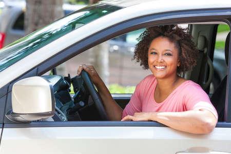 mujer alegre: Hermosa joven de raza mixta negro mujer afroamericana que conduce un coche