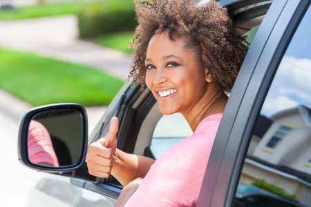 woman driving car: Beautiful young mixed race black African American woman giving thumbs up and driving a car