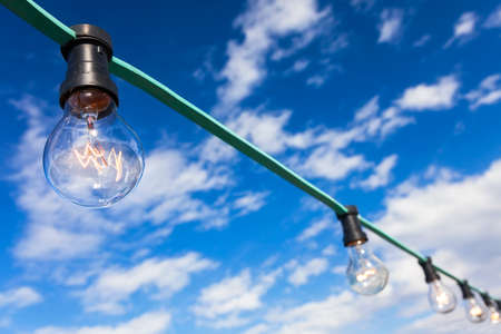 blue sky thinking: Blue sky thinking light bulb moment concept chain of filament bulbs
