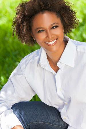 belle brunette: Belle jeune m�tis noir femme afro-am�ricaine avec des dents parfaites souriant et d�tente � l'ext�rieur dans le soleil d'�t� Banque d'images