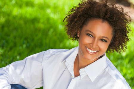 mujeres morenas: Joven de raza mixta negro mujer afroamericana hermosa con los dientes perfectos sonriente y relajarse al aire libre en sol de verano
