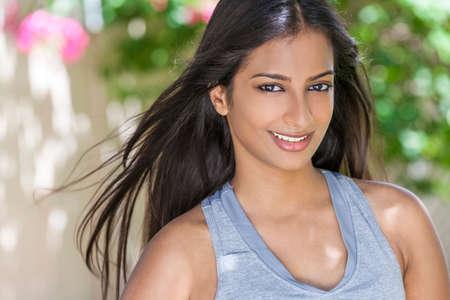 mujeres morenas: Retrato al aire libre de una hermosa mujer joven asi�tica india o ni�a al aire libre en sol de verano con los dientes perfectos y el pelo largo ejercer el uso de ropa de salud y fitness