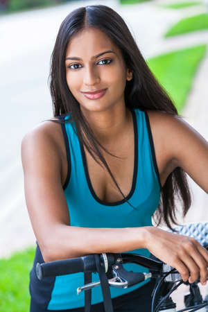 Outdoor fitness portrait of a beautiful Indian Asian young woman or girl outside in summer sunshine riding cycling her bicycle Banque d'images