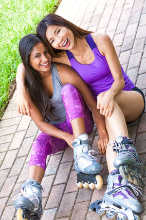 lesbian girls: Two young Asian women girls, Chinese and Indian, laughing having fun in line roller skating Stock Photo