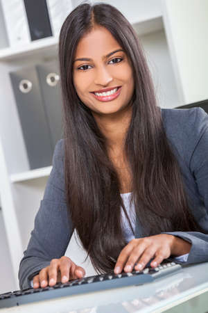 toothy smiles: Portrait of a beautiful young Asian Indian woman or businesswoman in office typing using a computer