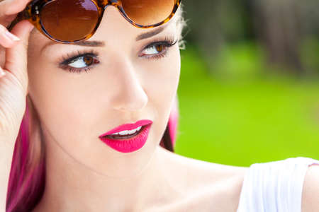 brown eyes: Outdoor portrait of a beautiful young woman or girl with brown eyes, blond and magenta pink hair wearing sunglasses