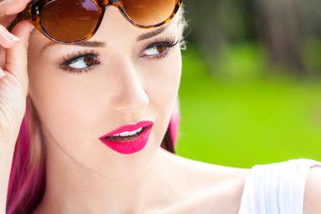 ojos marrones: Retrato al aire libre de una hermosa mujer joven o ni�a de ojos marrones, rubio y rosa magenta pelo con gafas de sol