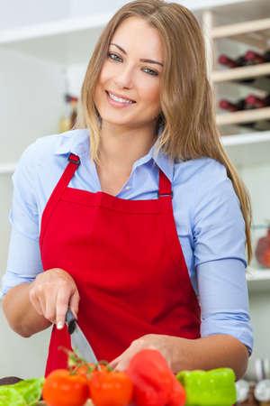 pimientos: Una hermosa mujer joven feliz o niña que llevaba un delantal rojo de corte y preparación de comida fresca ensalada de verduras en su cocina en casa