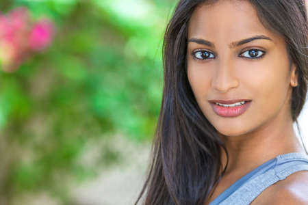 Outdoor portrait of a beautiful Indian Asian young woman or girl outside in summer sunshine